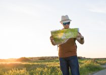 young man traveling and looking at the travel map PXNNZ93 1